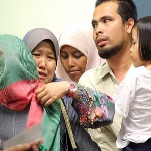 Nawal Iris' mother (in the green headscarf) being comforted by relatives. Pic: NST