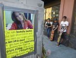 Marisol Meza, Ruben Mata and Tony Galvan, from left, stop to look at a street-side memorial for Kim Pham on Monday