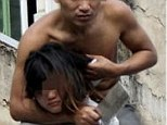A topless man gestures to police as he holds his girlfriend hostage with a knife atop a residential house in Sanya, Hainan province January 20, 2014