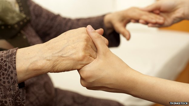 Old person holding hands with carer