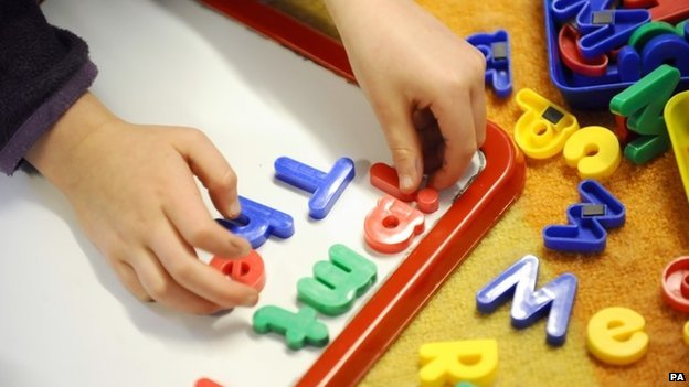 Primary school child plays with plastic letters